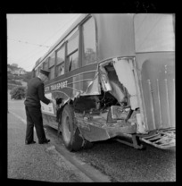 An unidentified bus driver inspecting a Wellington City Transport bus which has been in an accident, Karori, Wellington