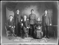 Studio family portrait with unidentified older parents and their four adult sons, youngest son in soldier's uniform standing between twin brothers, Christchurch