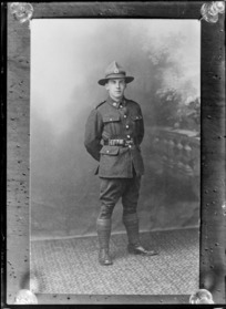 Studio portrait of unidentified young World War One soldier in uniform with 'NZ silver fern crown' collar and hat badges, Christchurch