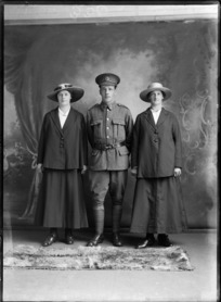 Studio portrait of unidentified World War I soldier with Liverpool collar and hat badges [Rifle Brigade Reinforcements?], standing between two women in hats, Christchurch