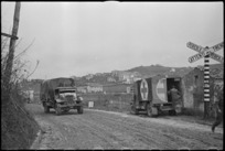Vehicles of 2 NZ Divison near a railway crossing on road near Italian Front lines, World War II - Photograph taken by George Kaye