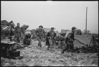 New Zealand Artillery personnel carrying ammunition through mud and slush on the Italian Front, World War II - Photograph taken by George Kaye