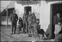 New Zealanders outside their temporary home with its civilian owners in an Italian village, World War II - Photograph taken by George Kaye