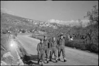 Soldiers walking on road near small Italian village of San Pietro, World War II - Photograph taken by George Kaye