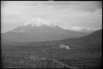 Enemy shell bursts on road in the Monte Cassino area with Monte Cairo in the background, Italy, World War II - Photograph taken by George Kaye