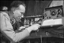 H L Willacy makes final adjustments to a wireless set on the Monte Cassino Front in Italy, World War II - Photograph taken by George Kaye