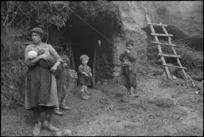 Civilian family outside cave in which they now live after their home was demolished by the Germans, Italy, World War II - Photograph taken by George Kaye