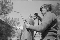 W A Boan adjusts pressure gauge on oxy acetone bottle at NZ Divisional Field Workshops, Cassino area, World War II - Photograph taken by George Kaye