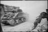 NZ Sherman tank making its way through the ruins of a village on the Cassino Front, Italy, World War II - Photograph taken by George Kaye