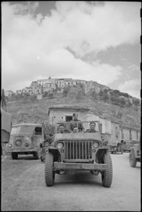 New Zealanders drive away from typical village on the Italian Front, World War II - Photograph taken by George Kaye