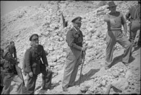 Prime Minister Peter Fraser pauses climbing Monastery Hill to ask General Bernard Freyberg a question about the recent fighting there, Cassino, Italy, World War II - Photograph taken by George Kaye