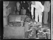 Unidentified baggage handler moving luggage from a Tasman Empire Airways Ltd flight, onto weighing machine, Auckland