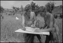 I E Gilbert and W S Tuck at work on artillery board in a wheatfield near Sora, Italy, World War II - Photograph taken by George Kaye