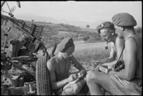 New Zealand anti aircraft gunners writing and chatting beside their gun near Sora, Italy, World War II - Photograph taken by George Kaye