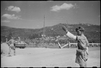 New Zealand Divisional Provost, I A Walker, directs NZ transport on way to Arezzo, Italy, World War II - Photograph taken by George Kaye