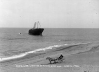Timaru beach, showing the wreck of the ship Elginshire, and a man in a horse-drawn cart in the foreground