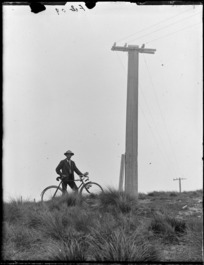 Owen Williams and bicycle on a tussock covered hill next to a power pole, Selwyn District, Canterbury Region