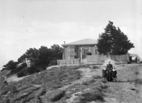 Woman and two boys, outside the house owned by William Moxham, on Upland Farm, Kelburn, Wellington