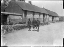 New Zealand soldier and two American soldiers walking past houses in Bertrancourt, France