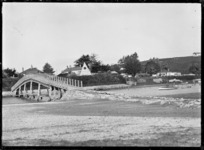 View of a footbridge over an inlet, with houses on the far side, probably at Raglan.