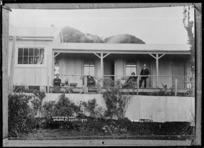 Group on the verandah of the caretaker's house, at Dawson Falls, Mount Taranaki - Photograph taken by David Duncan