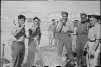 Members of the 28th (Maori) Battalion eating hangi-cooked potatoes on Christmas Day, Egypt - Photograph taken by George Robert Bull
