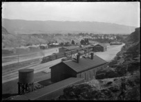 View over Cromwell township and railway station with a water tank in the foreground.