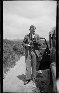 Man standing on roadside beside car