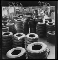 Interior of Dunlop rubber factory, Upper Hutt, showing stacks of tyres