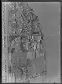 View over the New Zealand Refrigerating Company, Imlay Freezing Works Imlay Place, Wanganui, with stock pens and yards, showing Heads Road, Balgownie Avenue and Beach Road surrounded by residential housing, located beside the Wanganui River with wharf for loading ships