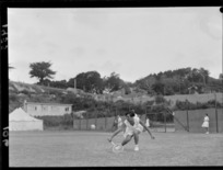 Unidentified woman competing on a grass court in a national tennis tournament, location unidentified
