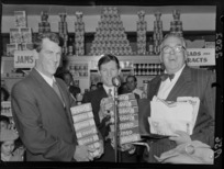 Unidentified man, with Sir Edmund Hillary and Selwyn Toogood, with give aways products of Rinso at the opening week of the Self Help store, Wellington