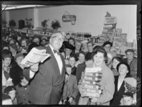Celebrity, Selwyn Toogood, and an unidentified shopper with the give away prize of Rinso, at the opening of the Self Help store, Lambton Quay, Wellington
