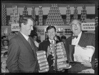 Unidentified man, with celebrities Sir Edmund Hillary and Selwyn Toogood, with give away products of Rinso at the opening week of the Self Help store, Lambton Quay, Wellington