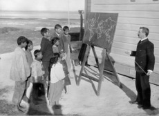 Teacher, outside with a blackboard, taking a geography class