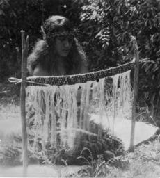 Māori woman weaving taniko