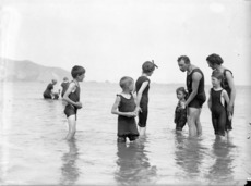 A group in bathing costumes, paddling in shallow water