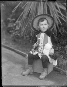 [Owen William Williams?], sitting on a wooden box, with a puppy and toy trumpet, location unidentified