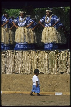 Little boy walking in front of Tokelau performers at the 8th Festival of Pacific Arts, Noumea, New Caledonia