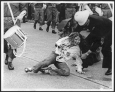 Woman demonstrator being dragged by a policeman