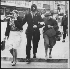 Policeman escorting two women across a street, Wellington