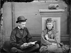 Unidentified man reading a book, and an unidentified woman