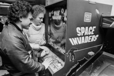 Young man and woman playing space invaders