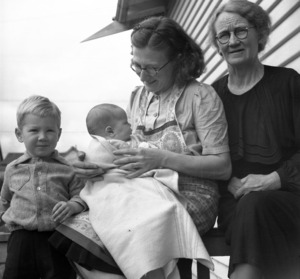 A family from Kumara, Westland, including a young boy, a woman holding a baby and an older woman