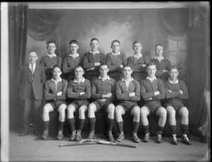 Studio portrait of a men's hockey team, unidentified players in uniforms and coach with hockey sticks in front, Christchurch