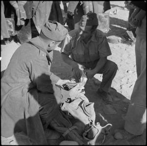 NZ officer examining possessions of Italian POW