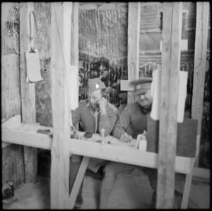 Two NZ officers at work in office dugout in the Western Desert