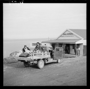 Two women sitting on the back of a utility vehicle outside Walker Bros general store, Te Kaha