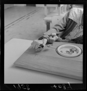 A student eating lunch with the assistance of a mechanic aid to hold cutlery, at Kimi Ora School for children with special needs, Thorndon, Wellington