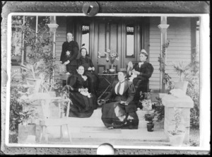 Group of five unidentified women on the steps of a house, two of the women are doing crochet and one woman knitting, various pot plants can be seen on the steps and in front, probably Christchurch district